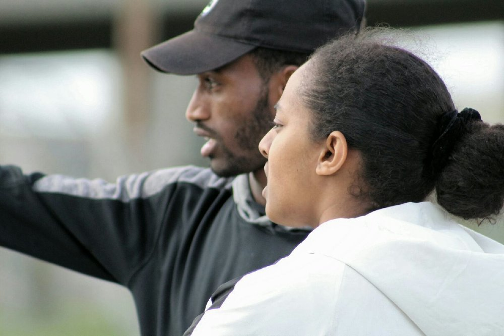 Lady Eagles Head Coach Yohannes Harrish discusses game strategy with his soccer players. (Photo by Edwin Flores)