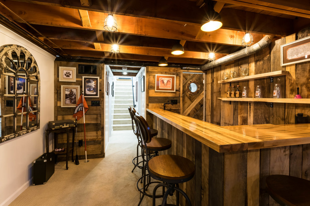 AFTER-An ultimate western basement bar, complete with recycled barn wood, a custom bar top, and putting cups
