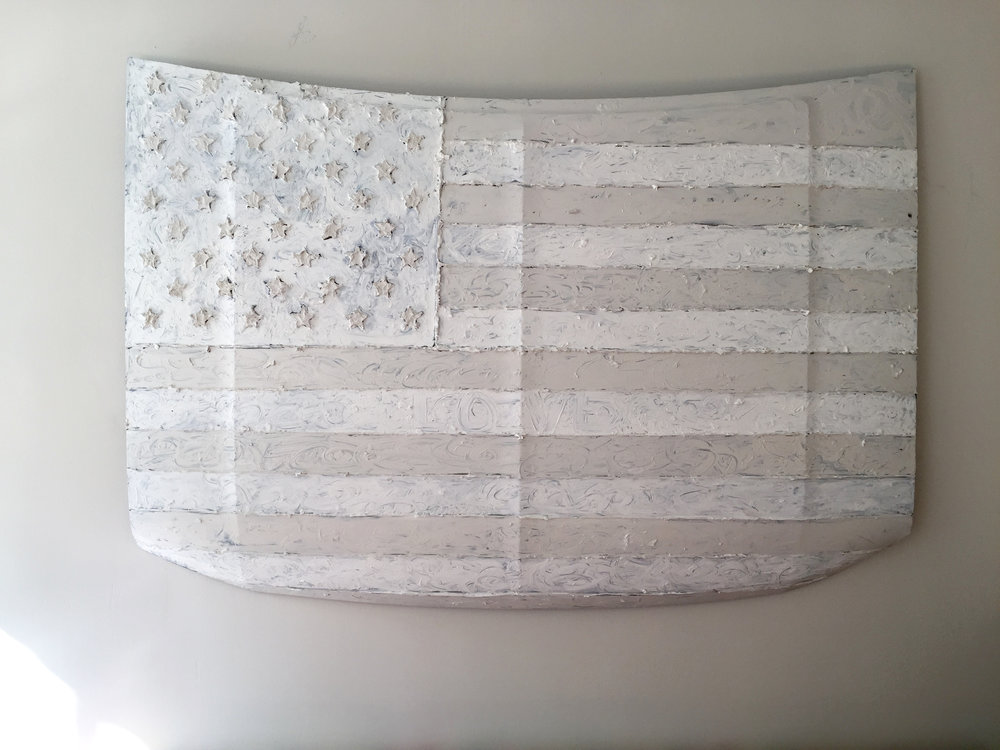This is my first piece, a white american flag.  This piece is called WHITE FLAG ONE LOVE.  It is oil on metal.  The stars and the lines between the stripes are raised up off of the metal hood.   The origination of the piece is a Ford F-150 pick up truck hood from the 90's.  It is 66x44x6