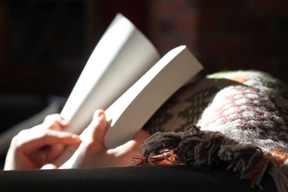 woman-reading-book-in-bed-under-blanket.jpg