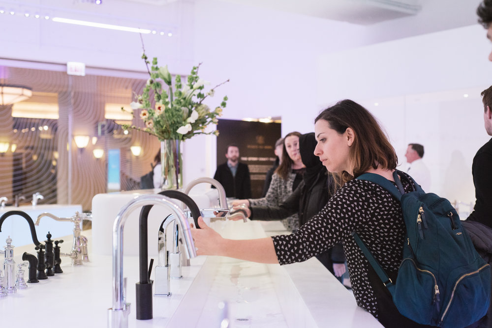 Romina tests an Align Matte Black Kitchen Faucet at the Moen showroom