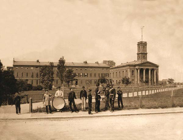A band poses in front of Naval Terrace and the Dockyard Church