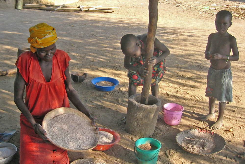 A mother and her children pound millet in South Sudan