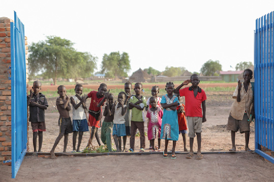 Children wait outside the South Sudan Community Bank.