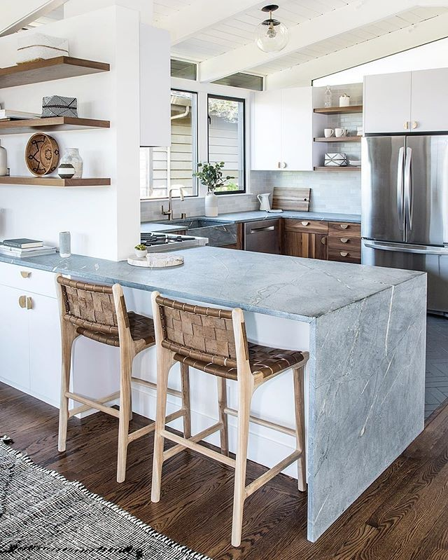 This kitchen from @saffronandpoe features an unfinished soapstone waterfall peninsula with a matching trough sink. The woven leather strap counter stools tie all the natural elements together. Follow along on their #millvalleymidcentury project to see more. 😍 — Interior Design: @saffronandpoe —  #myscoutandnimble #roomforinspo #howyouhome #designinspo #homedesignideas #hgtvhome #smmakelifebeautiful #ruedaily #elledecor #maketimefordesign