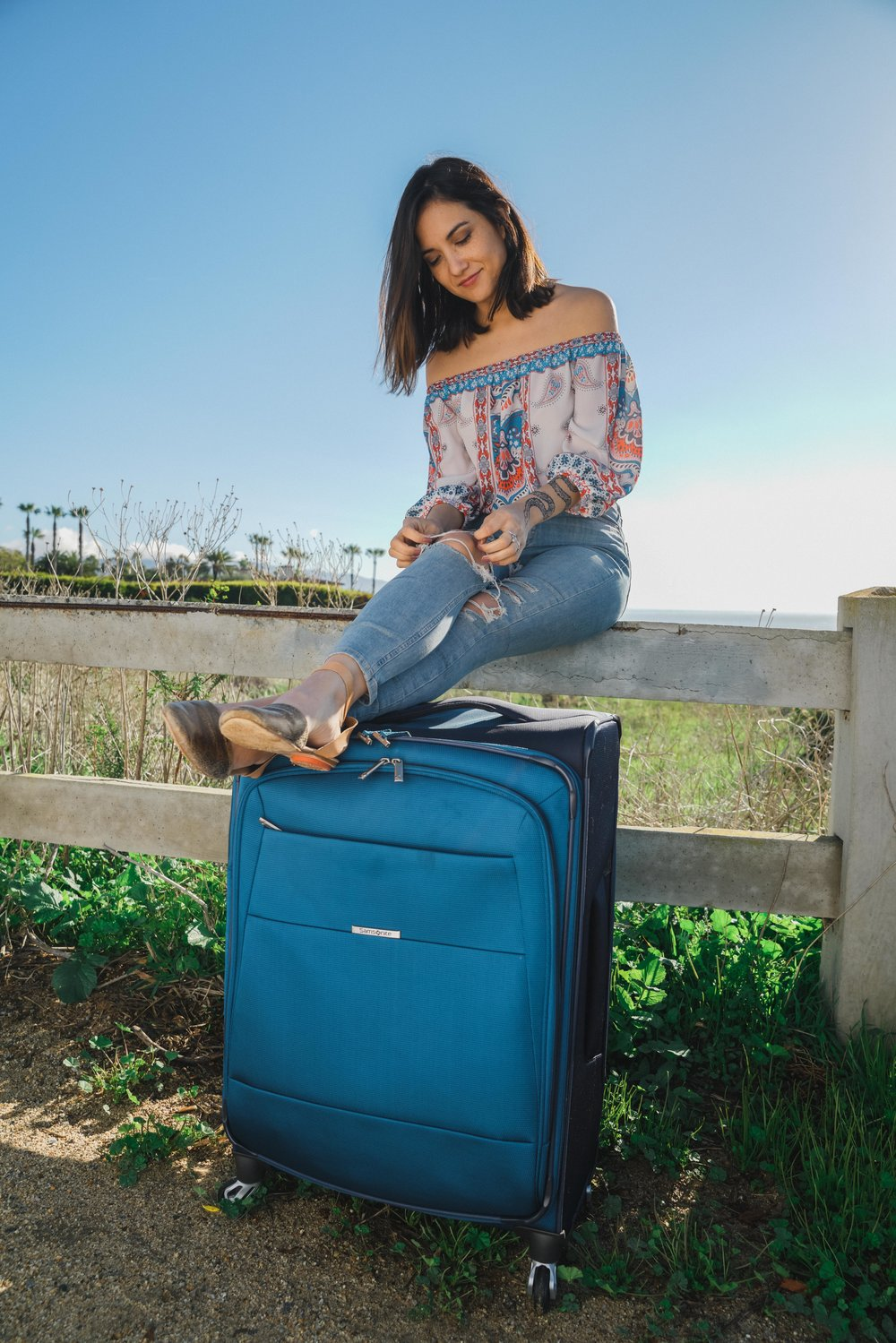 Benita Robledo by the beach travel with suitcase