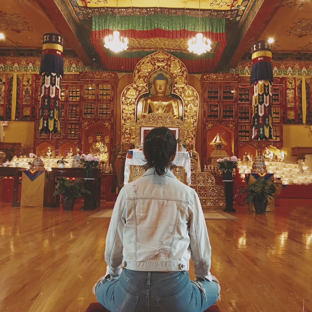 brunette meditating jean jacket budhist temple