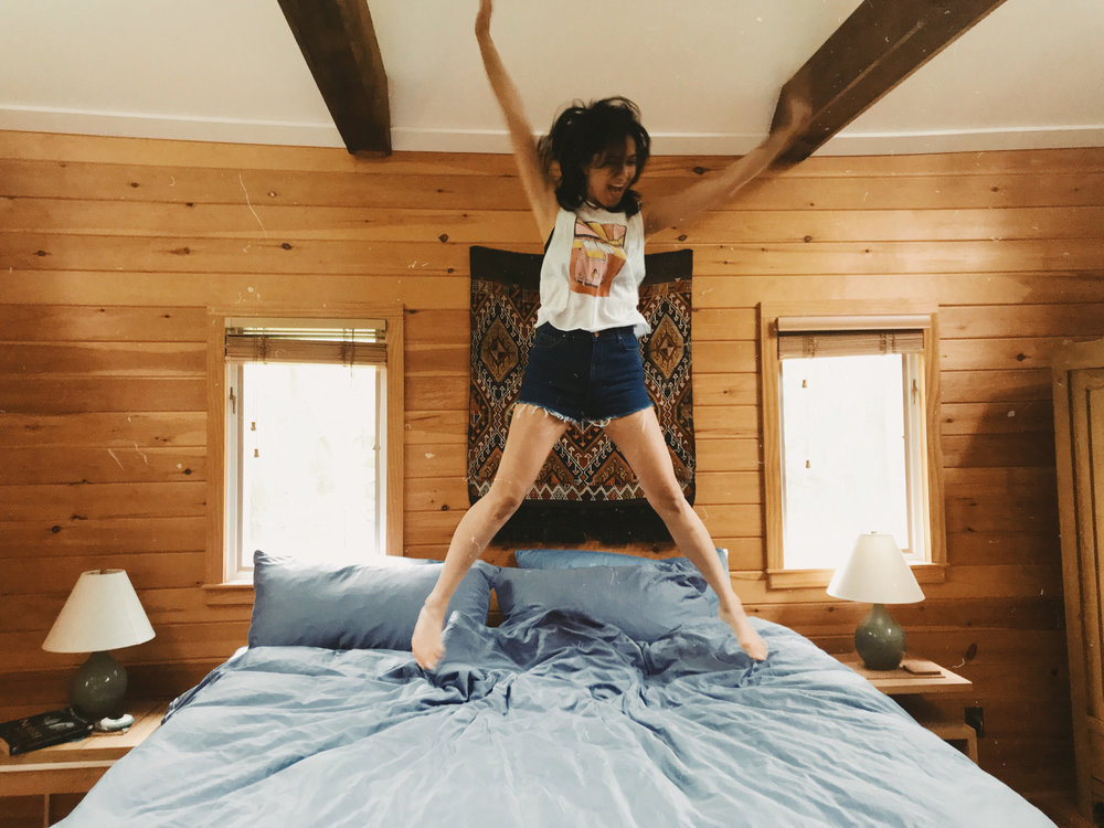 fashion blogger jumping on a bed