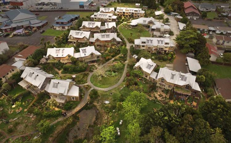 Aerial view of   Earthsong Eco-Neighborhood    in New Zealand. 32 homes sit in just over 3 acres. This multi-generational community accommodates a variety of households living in 1-bedroom studios to 4-bedroom houses. Key features are sustainable construction, extensive food gardens and orchards, car free grounds around the houses and play areas for children. (Photo: cohousing.org.nz)