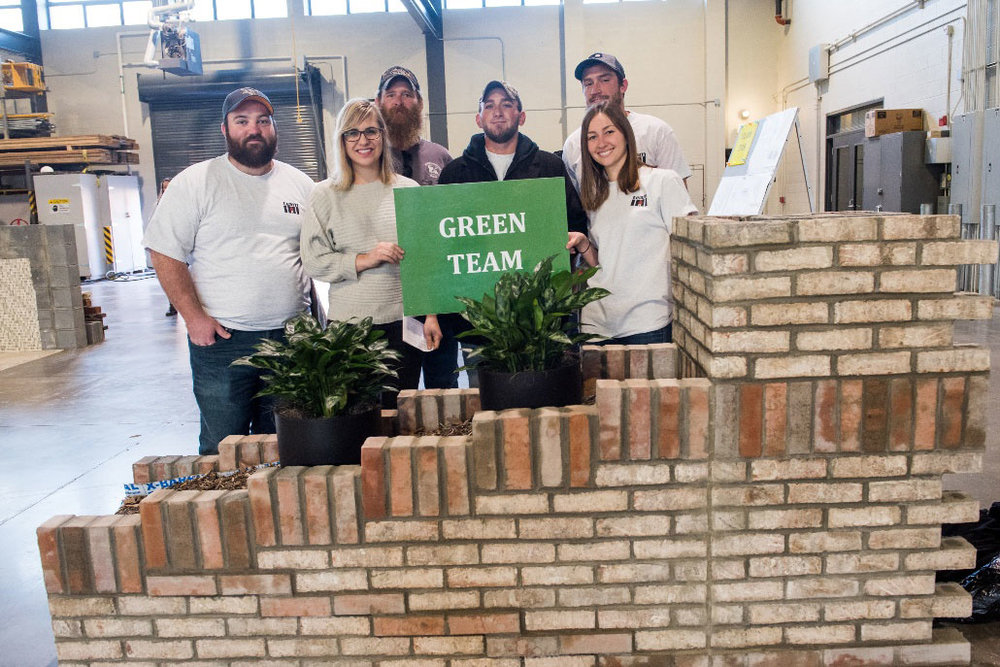 Kelsey Holmes with her fellow Green Team members with their finished project, which incorporated a custom drain solution to allow plans to grow between healing spaces in their center.