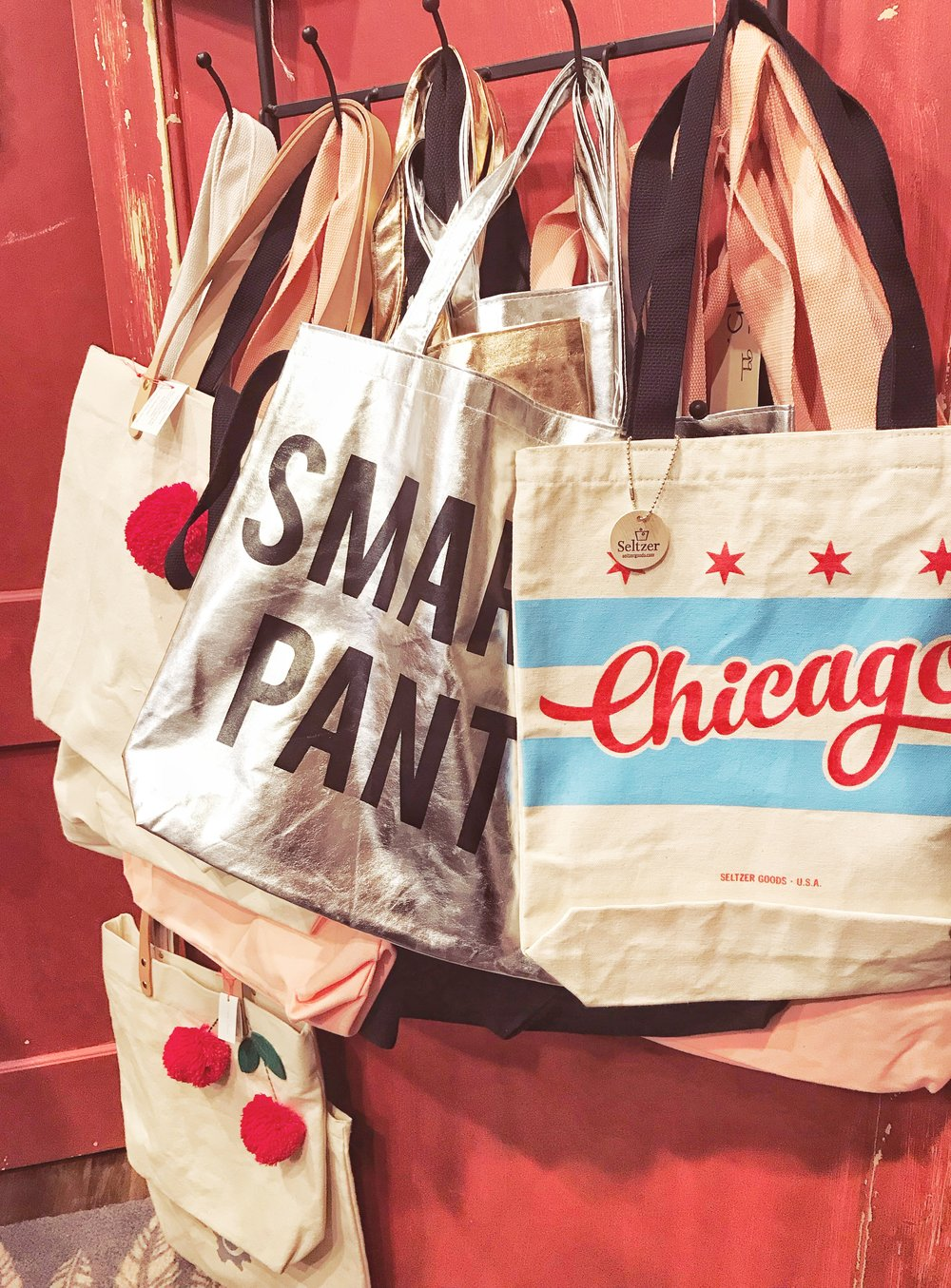 Meri Meri Tote with red cherries, $49.99; Smarty Pants Tote by Santa Barbara, $9.99; Chicago Tote by Seltzer, $19.99 - (Pictured from left to right.)