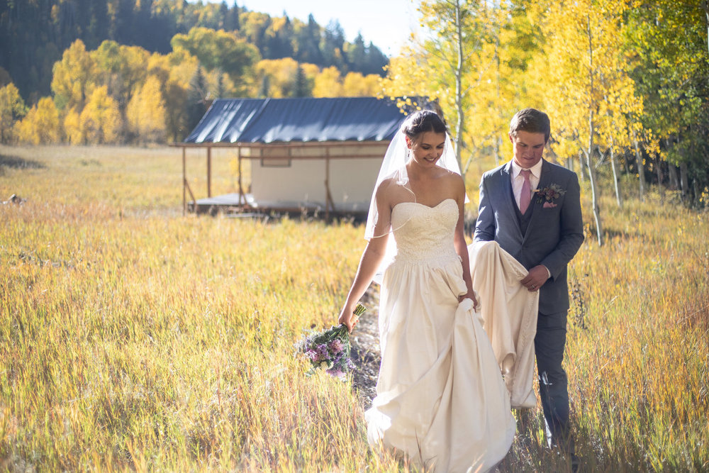 Bride and Groom walking away from their wedding tent near Durango, Colorado