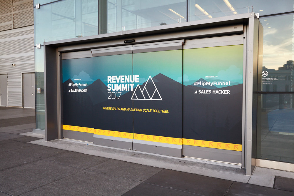 Window clings applied to the exterior of a venue can really make a strong impact as attendees arrive at your event. For Revenue Summit, a sales and marketing conference with 1200+ attendees, event branding started on the doors of Pier 27 in San Francisco.