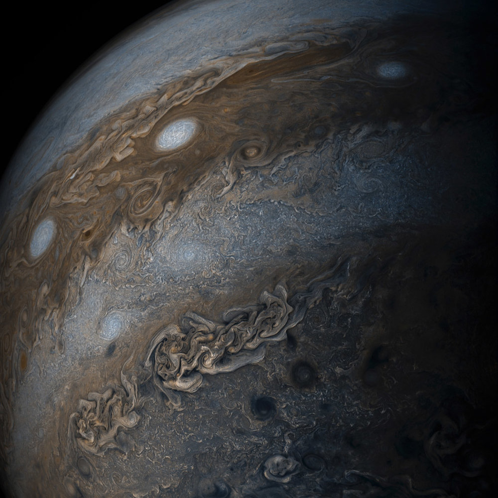 """Three of the white oval storms known as the """"String of Pearls"""" are visible near the top of the image. Each of the alternating light and dark atmospheric bands in this image is wider than Earth, and each rages around Jupiter at hundreds of miles (kilometers) per hour. The lighter areas are regions where gas is rising, and the darker bands are regions where gas is sinking. NASA"""