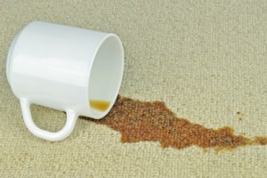 A spilled cup of coffee on a carpet with stain