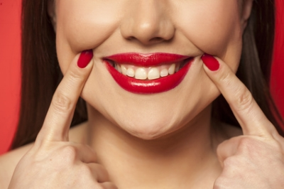 woman forcing smile with fingers.jpg