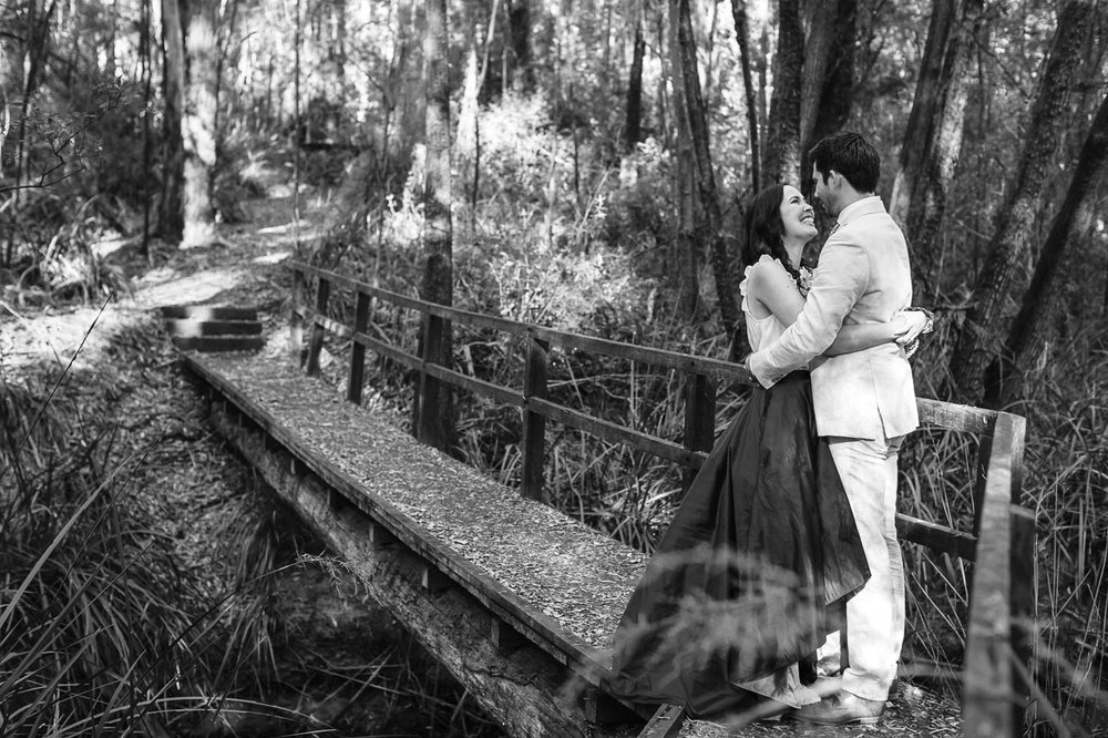Nic Duncan portrait and wedding photographer, bride & groom on a bridge in the forest