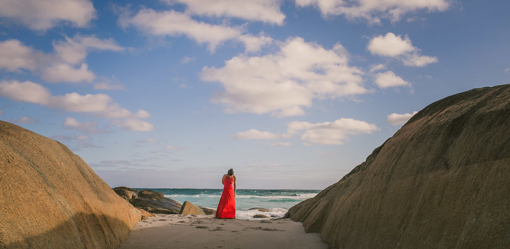 Portrait of a woman in a red dress, on the beach