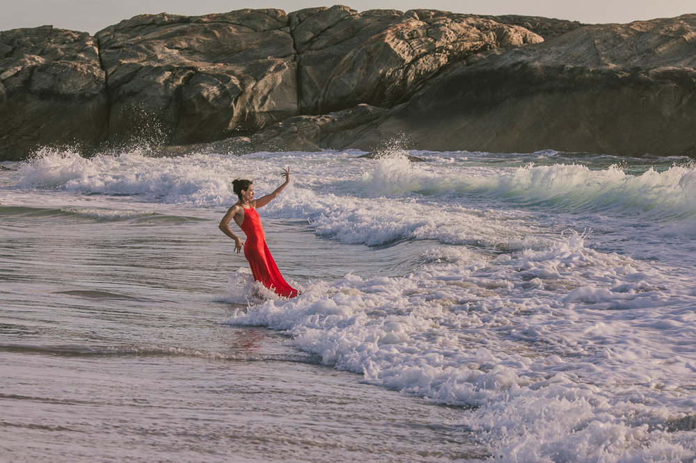 Fire and water, portrait of a lady wearing a red dress in the ocean