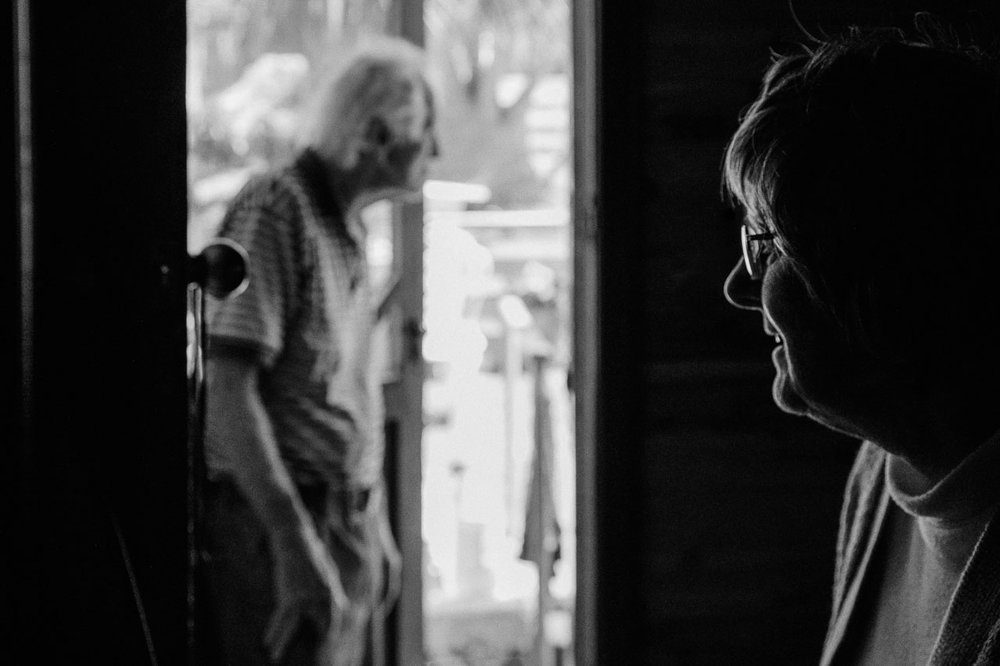 Old man at the door as his wife watches him