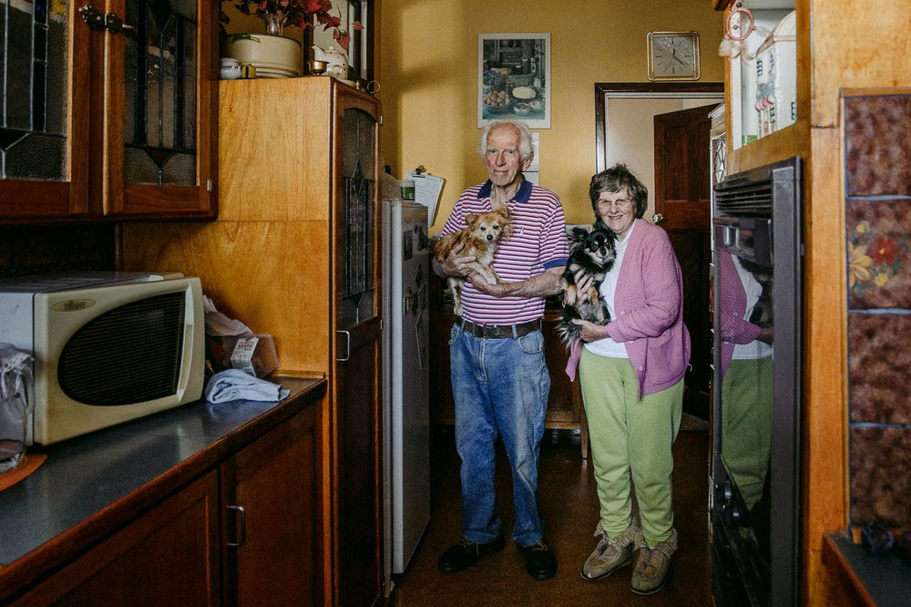 Elderly couple in their kitchen with their two small dogs
