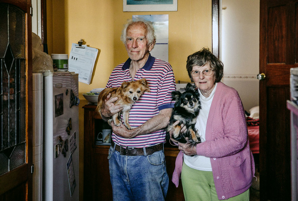 Portrait of two elderly people holding their small pet dogs