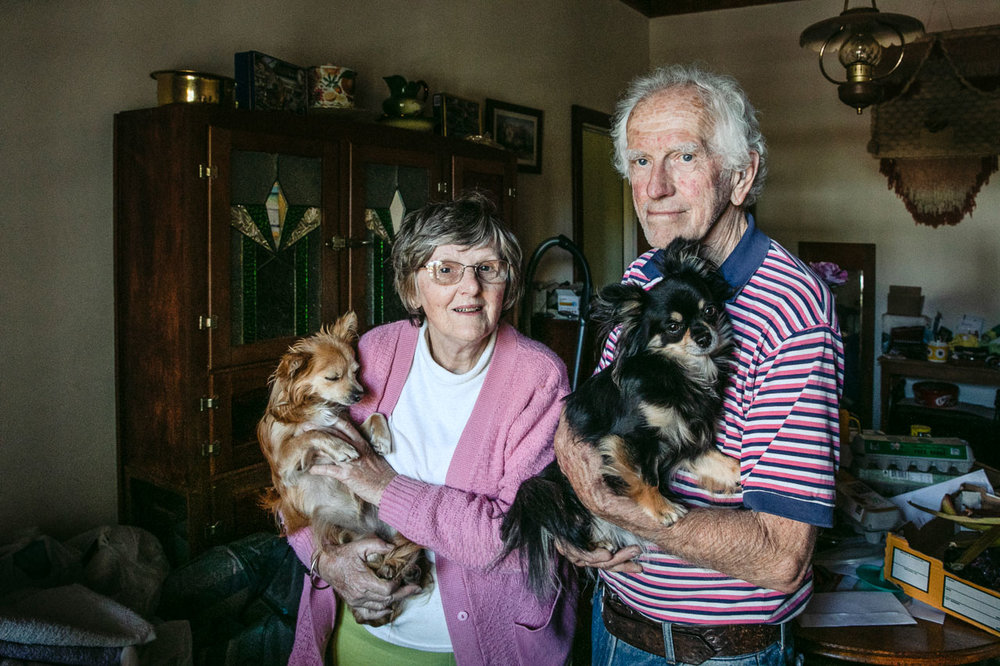 Portrait of an elderly couple holding their small dogs at home