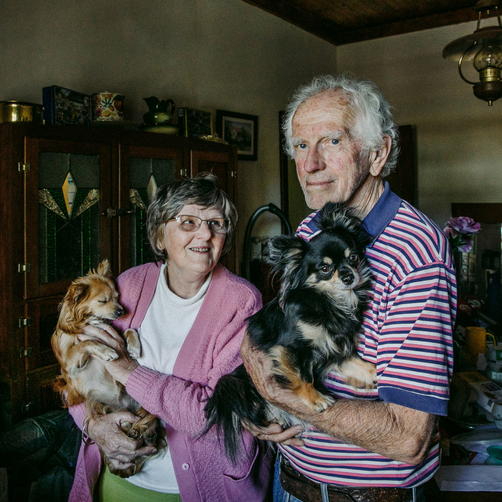 Elderly couple at home with their pet dogs