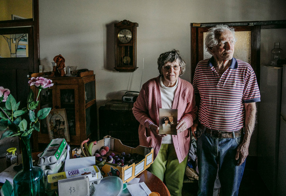 At home with an elderly couple with the wife holding their wedding photo