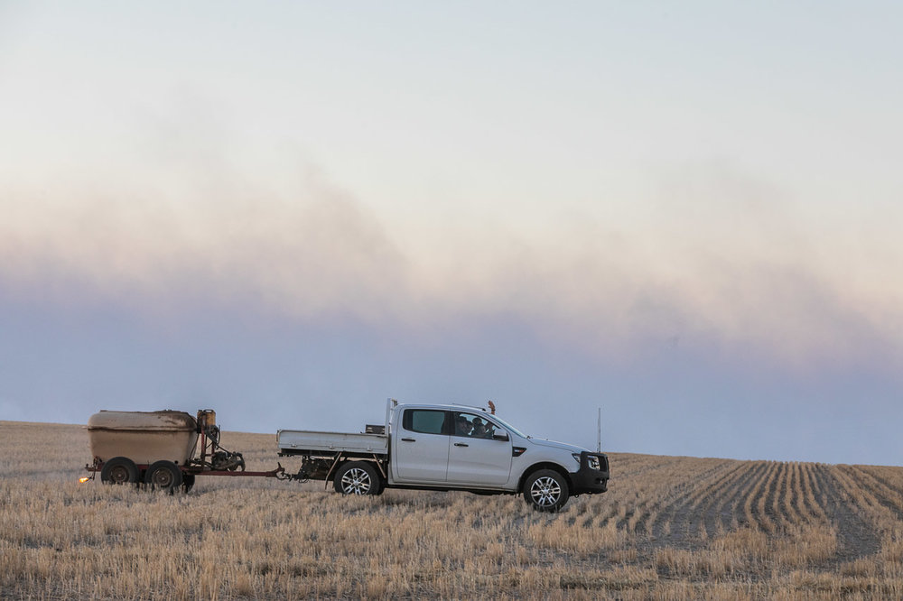 The farmer in his ute setting fires for windrow burning in the wheatbelt