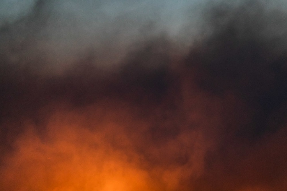 The glowing fire and smoke during windrow burning