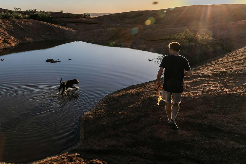 Rim lit man and dog at sunset with pool of water
