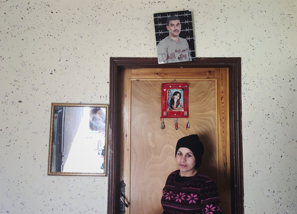 Sameera smuggled her husband's sperm from an Israeli prison. She's standing in her kitchen beneath a photo of her 11 year old daughter who died in a car crash and her husband who's been in prison for 14 years. Story published by Snap Judgment.