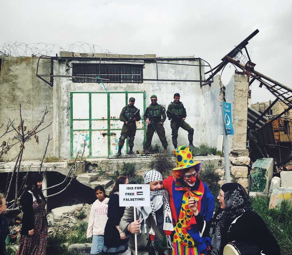 "A fringe group of settlers in the West Bank city of Hebrom celebrating Purim.  Costumes from left to right: terrorist, clown and ""Palestinian woman."""