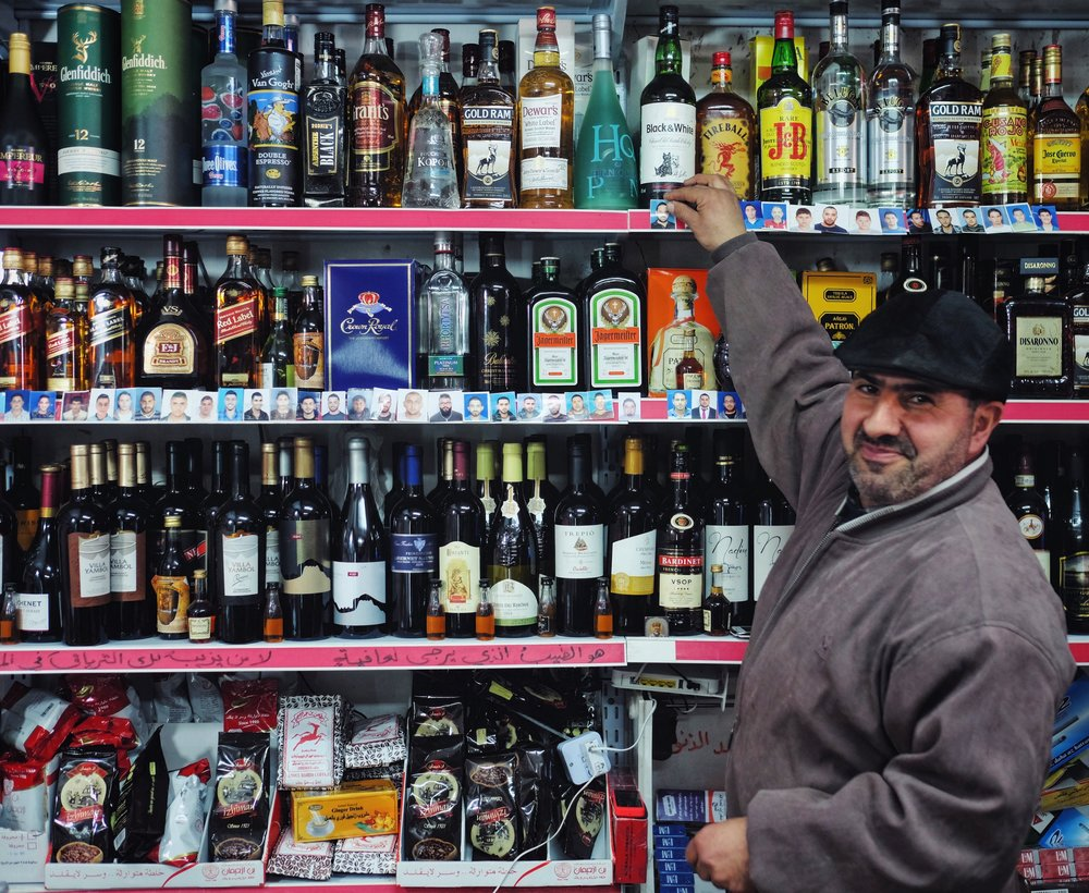 A West Bank liquor store, but if you look closer you'll see boys' passport photos lining the shelves. The boys in Taybeh want to go to America so they bring their pics to Sarri, a US citizen and owner of this shop. He moves the pictures from the bottom row to the top when the boys leave for the US.