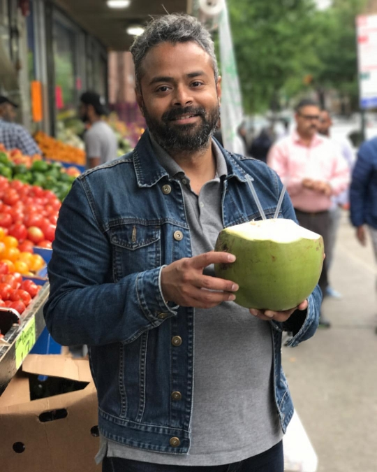 Dhrubo with our coconut-for-two, hacked before our eyes on 37th Avenue.