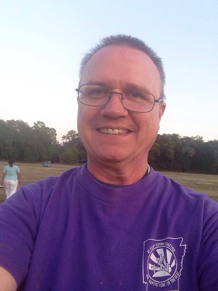 Glenn is holding his phone and taking a picture of himself. He has short dark brown hair and wears glasses. He is wearing a purple shirt that has a logo on the top left on the front of the shirt.