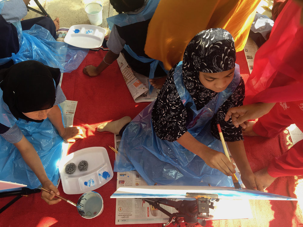 An aerial view of a girl applying blue paint to her canvas, assisted by a volunteer.