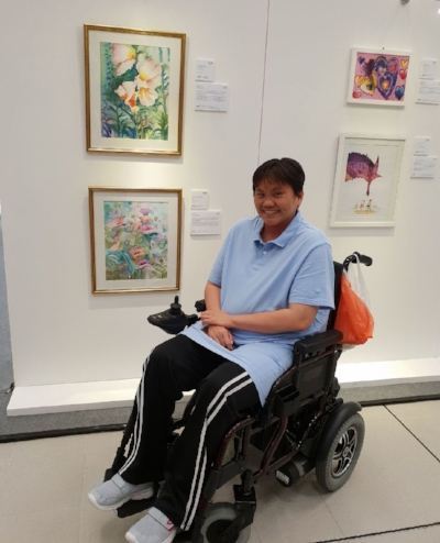 Painter Christina Lau Lay Lian smiles in front of two of her floral masterpieces. She sits in an automated wheelchair, wearing a light blue polo shirt and black track pants.