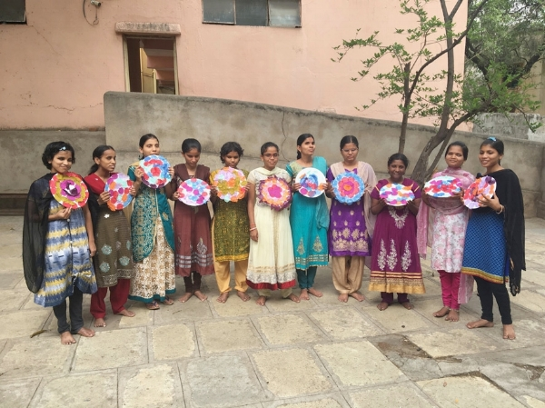 All eleven girls stand in a row in the school courtyard, holding their artwork in front of their chests and smiling.