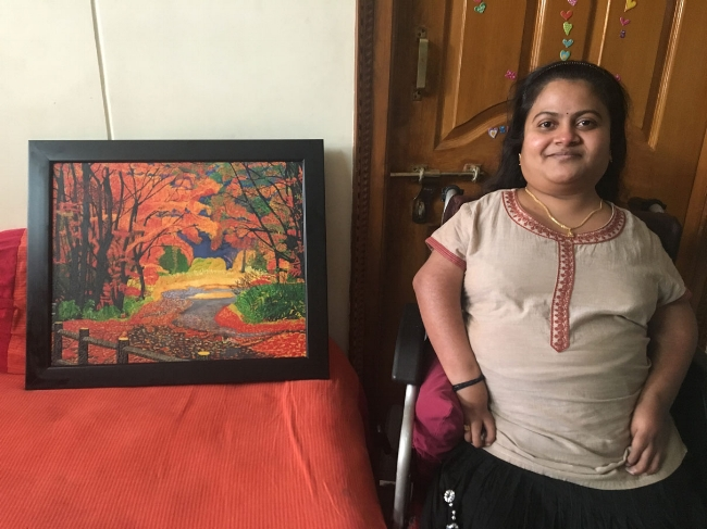 "Srilekha Mandalapalli next to her recently sold oil painting, ""Rebirth - Celebrating the Spirit of Motherhood."""