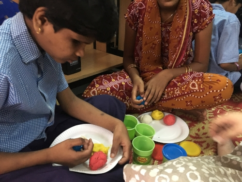 A student feels a ball of blue play dough in her right hand, holding a plate with red, white, and yellow dough with her left hand.