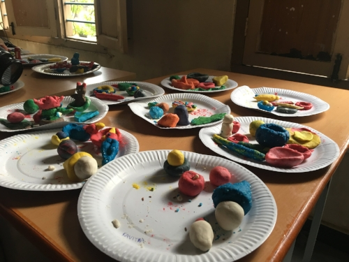 Several plates of colorful play dough creations laid out to dry.