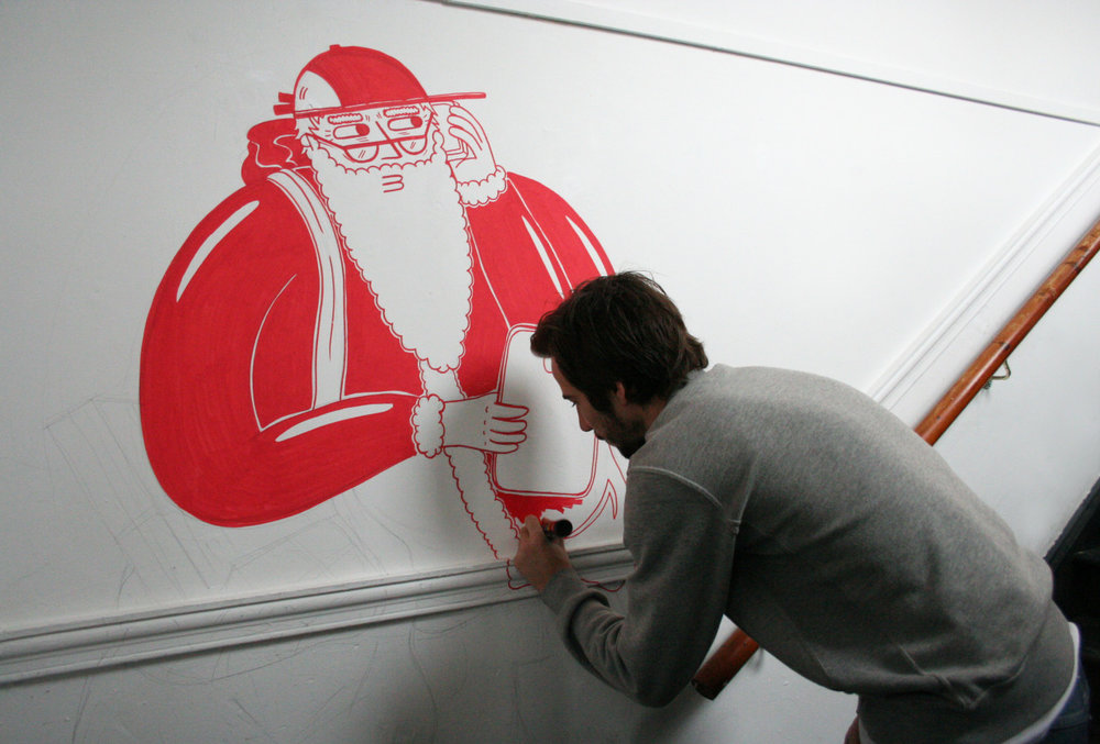 Henry Boon  is back at  The Birdcage  again! This time he is transferring his Christmas card design for  Deck The Halls  onto the walls of  The Bridge . Check out more work-in-progress and detailed shots of Henry's version of Santa on his website    www.hbillustration.4ormat.com   .