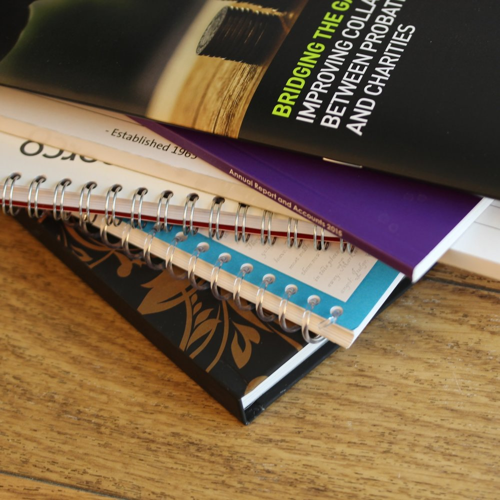 Pile of books bound in a variety of ways, such as coiled, stitched and pad glued
