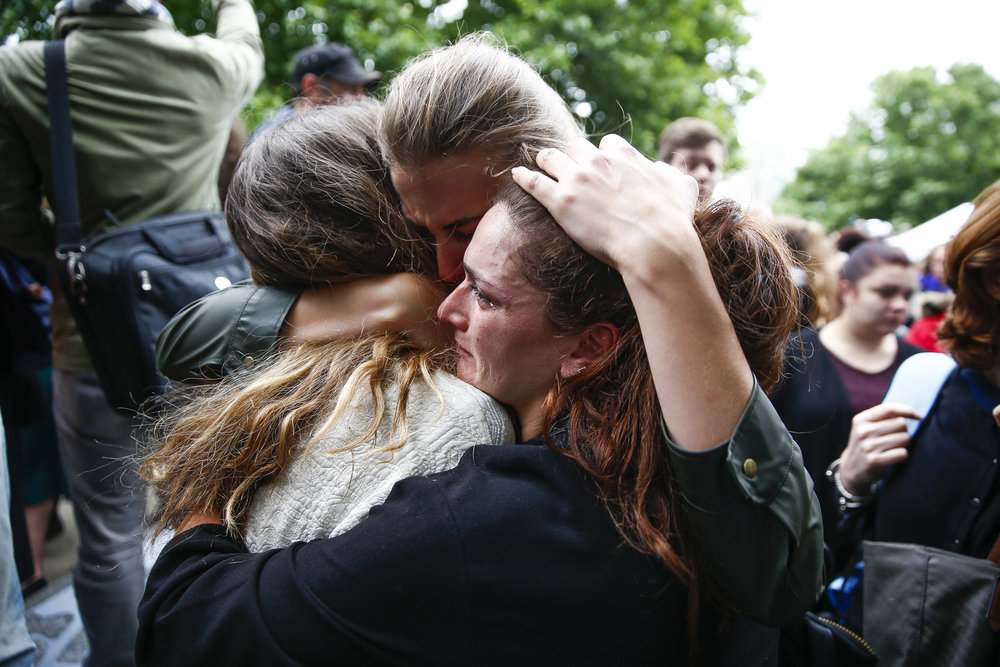 People embrace following a vigil in London to remember those killed in the London Bridge terror attacks.