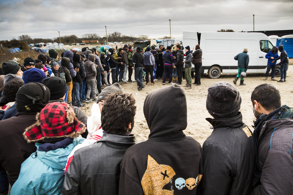 Dozens on migrants queue for food handouts in the Jungle Camp in Calais.