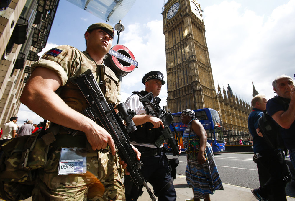 A British soldier joins police on guard outside the Houses of Parliament, London.
