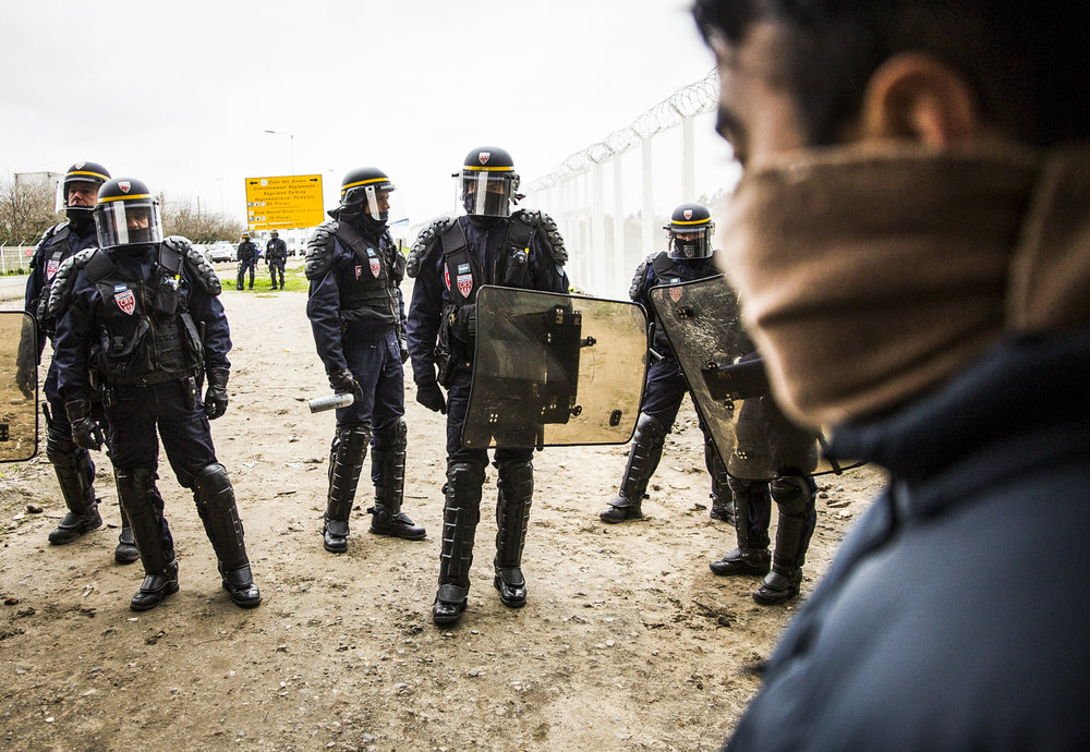 Police guard the entrace to the Jungle Camp in Calais during a protest against the death of a young migrant on a motorway.