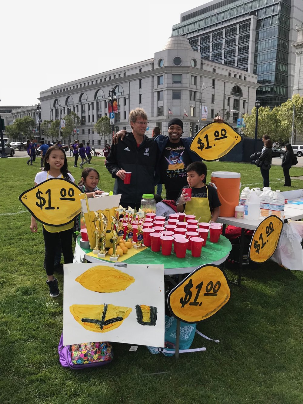 The Tenderloin Recreation Center team with Coach Marquis and SCORES CEO Colin Schmidt sell lemonade at game day to raise money for Glide Memorial Church.